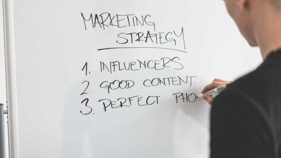 Marketing Expert Writing New Strategy on Whiteboard