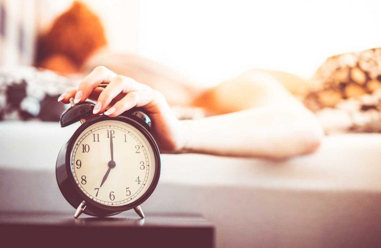 Woman Shutting Off Ringing Alarm Clock