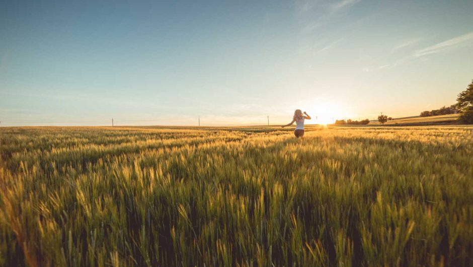 Young Woman Running Through Wheat Field on Sunset