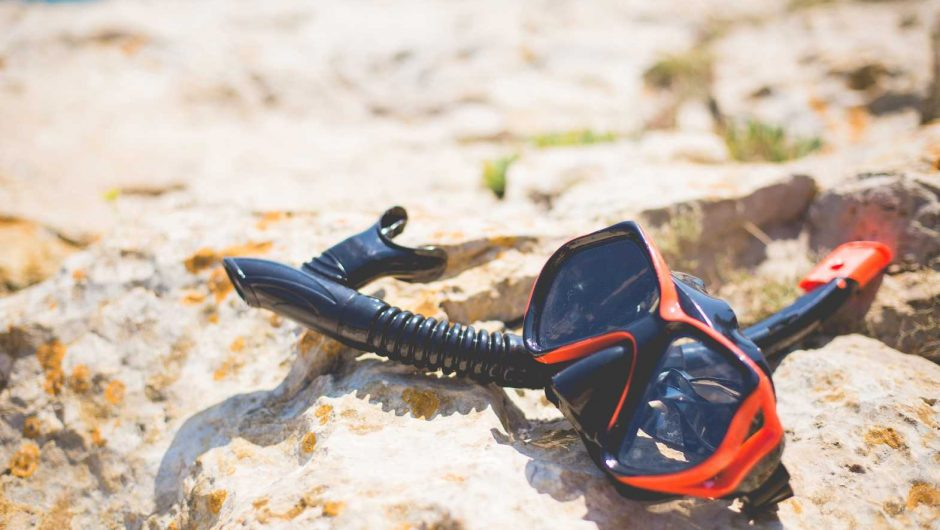 Snorkel and Diving Scuba Mask On a Rock Near The Sea